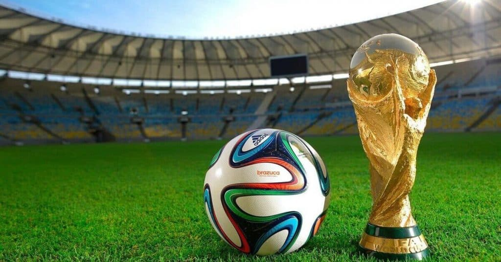 soccer world cup trophy and official soccer world cup soccer ball sitting on the grass in a brand new stadium